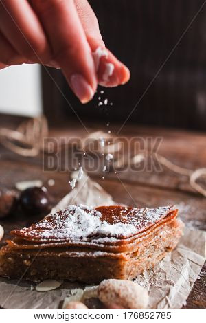 Confectioner sprinkling baklava with sugar powder. Closeup of baker hand finishing preparation of traditional turkish dessert. Sweet, eastern cuisine, pastry concept