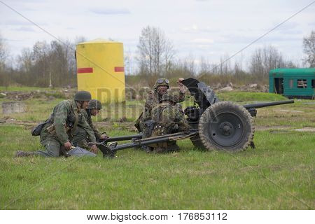 LENINGRAD REGION, RUSSIA - MAY 05, 2015: German soldiers firing from anti-tank guns. Reconstruction of the episode of the great Patriotic war