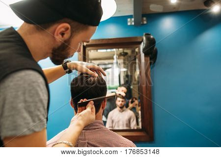 Young stylist cut client at mirror free space. Man sitting in chair while barber shaving him with trimmer. Beauty, style, modern life concept