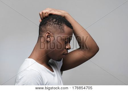 Thoughtful young african american guy looking down on grey background. Finding way to solve problems with free space for text.