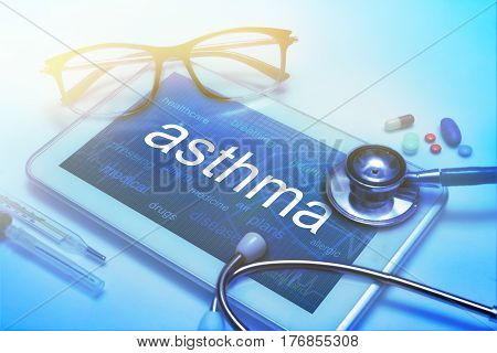 Asthma word on tablet screen with medical equipment on background