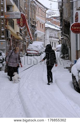 VELIKO TARNOVO BULGARIA - JANUARY 6 2017: Unidentified woman walks her dog down the snowy street of the town in the winter