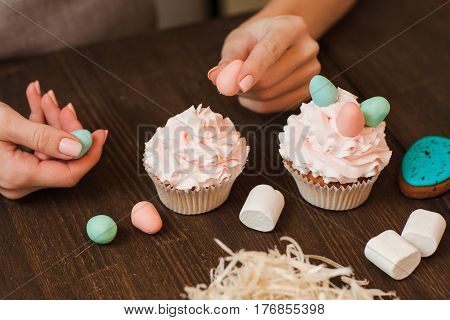 Masterclass of preparing decorated cupcakes with white cream on wooden table. Cookery arts. Easter gift, small business, delivery of sweets, craftmanship concept