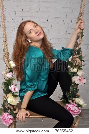 A girl with red hair in a green blouse sits smiling on a swing with flowers
