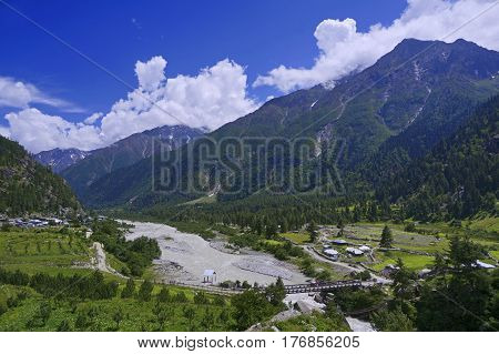River amidst Forest-Covered Mountain Ranges in the Village of Rakcham Situated in the High-Altitude Mountain Region of the Kinnaur Valley in the Himalayas, Northern India.