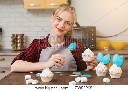 Young smiling woman cooking homemade cup cakes in kitchen. Culinary masterpiece. Easter gift, small business, delivery of sweets, craftmanship concept