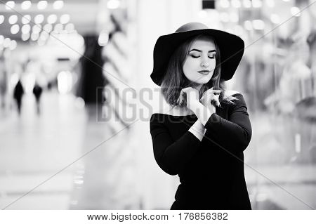 Fashion Red Haired Girl Wear On Black Dress And Red Hat Posed At Trade Shopping Center.  Black And W