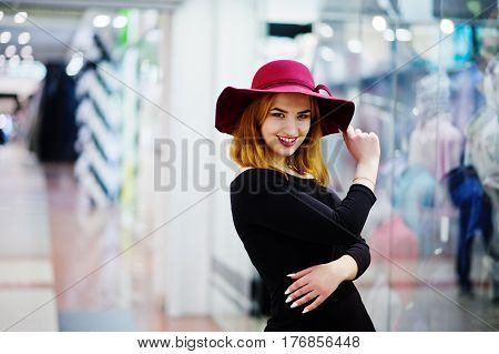 Fashion Red Haired Girl Wear On Black Dress And Red Hat Posed At Trade Shopping Center. Photo Toned