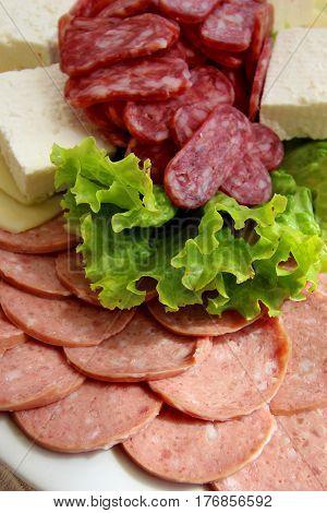 Sausage slices with lettuce leaf  - close up