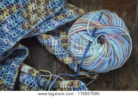 Knitting a scarf from a multi-colored six on a wooden background. Multicolored pattern, warm, cozy.