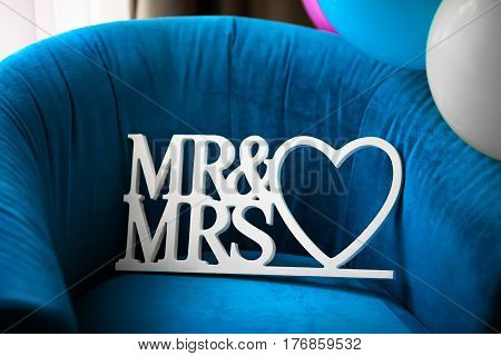 Beautiful wedding Mr and Msr label with heart on blue armchair, closeup