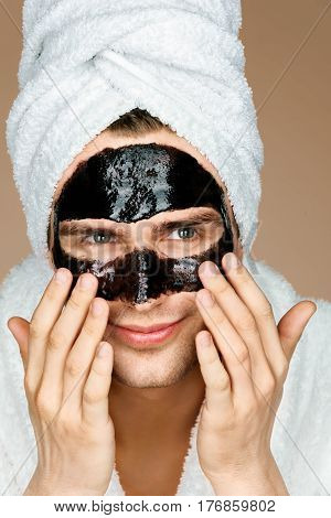 Handsome man with black face mask on his face. Photo of smiling man receiving spa treatments. Grooming himself
