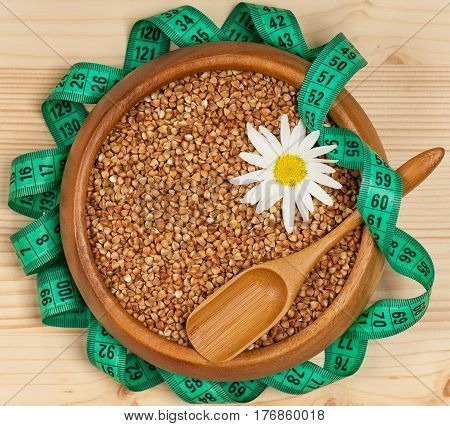 Raw buckwheat in a bamboo bowl with tape measure on a wooden surface