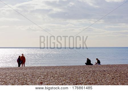 BRIGHTON GREAT BRITAIN - FEB 24 2017: People looking at the sea at the Brighton beach. February 24 2017 in Brighton Great Britain