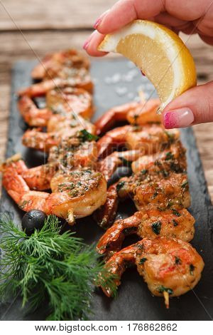 Preparing Mediterranean food - Chef hand squeezing lemon on appetizing fried shrimps served on black slate, close up view