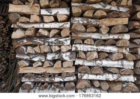 Woodpile of birch wood with a pattern of longitudinal and transverse pieces of wood