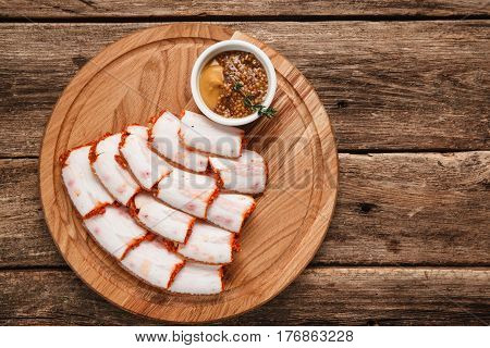 Ukrainian salo served with mustard, top view. Background of rustic wooden table with free space for text.