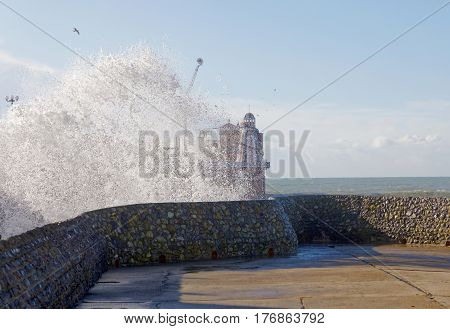 Large waves hit the Brighton beach splashing over wall the Brighton pier in the background