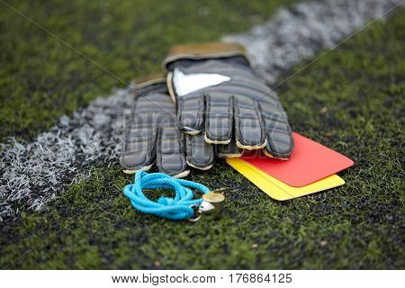 sport, soccer and game - gloves, goalkeeper referee whistle and caution cards on football field