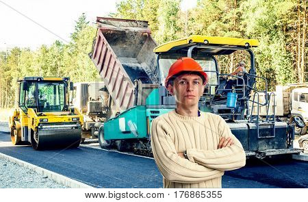 Workman in red helmet with asphalt-placing machine