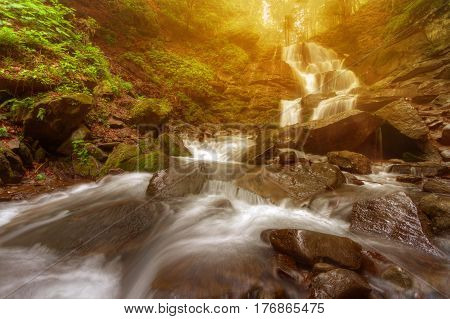 Amazing beauty of Alps mountains waterfall. Summer waterfall in Alps with soft sunlight at evening