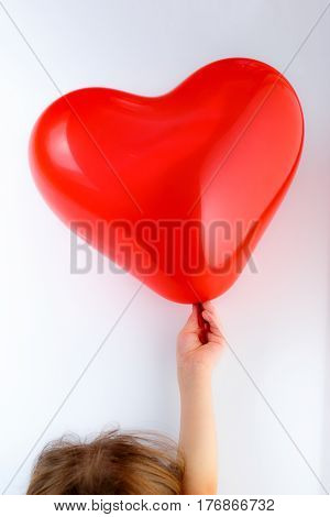 Red Heart Balloon In Child's Hand