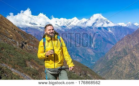 Happy bearded Hiker in yellow Jacket holding Tea Mug smiling and looking up on surrounding Mountain View