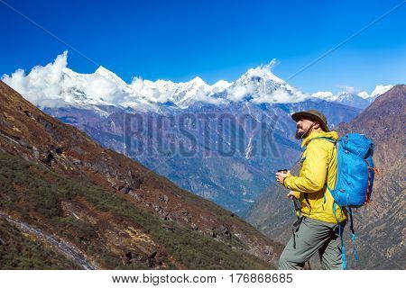 Cheerful bearded middle age Hiker in Yellow sporty Jacket and blue Backpack standing on Trail and looking up. Mountain high Peaks Panorama on Background