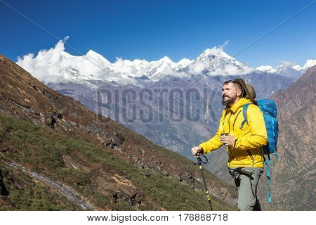 Cheerful bearded Hiker in yellow Jacket holding Tea Mug smiling and looking up on surrounding Mountain View