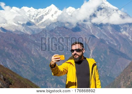 Bearded Man in bright sporty Jacket taking Photo Self Portrait or Video with mobile Telephone holding it in Hand in front of Mountain Panorama