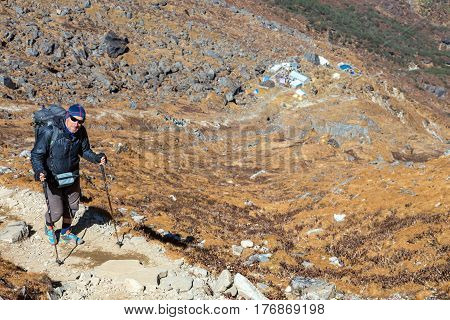 Smiling senior Person in sporty Clothing and with Backpack walking up on steep Mountain Trail from Lodge visible far down