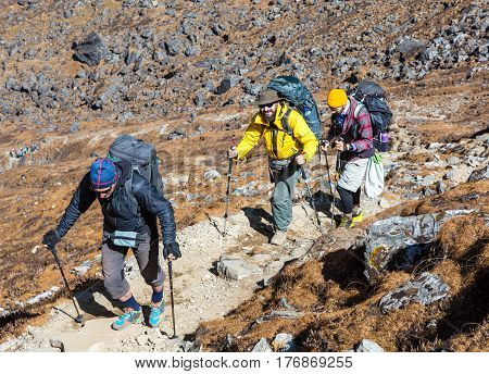 Group of People of different age in bright sporty Clothing walking up on Mountain Trail during Trekking in Nepal Himalaya with high Peaks and Rocks on Background.