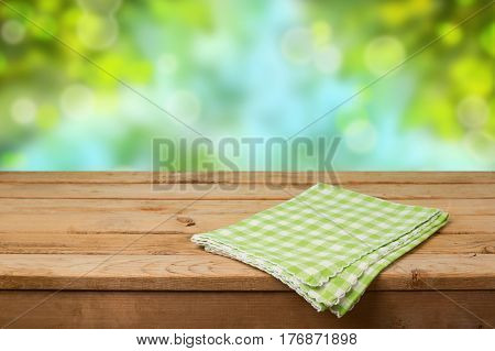 Empty wooden deck table with checked tablecloth over green nature bokeh background for product montage display