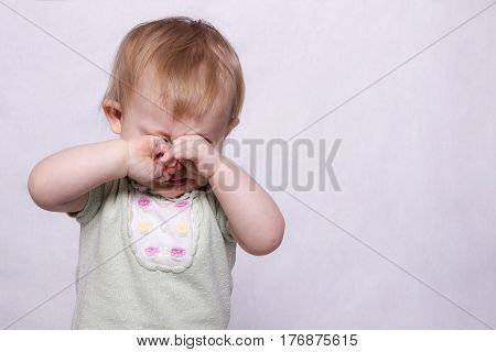 Adorable baby girl crying on the monochrome background. Horizontal studio shot. Copy space