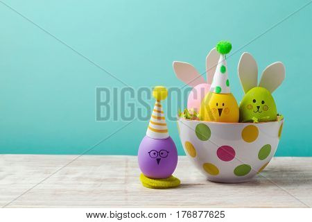 Easter holiday concept with cute handmade eggs bunny chicks and party hats in bowl on wooden table