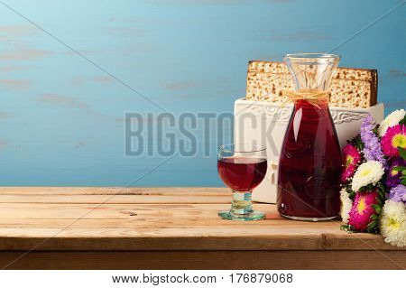 Jewish Passover holiday Pesah celebration concept with matzoh and wine over blue background