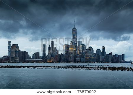 New York City Financial District skyline in early morning from across the Hudson River. Low storm clouds over the skyscrapers of Lower Manhattan