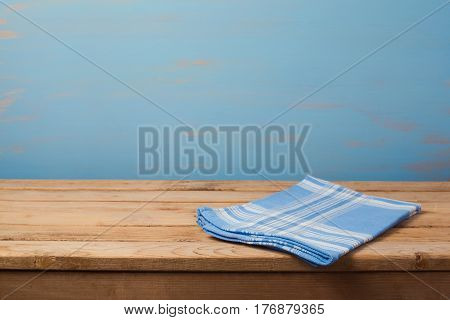 Empty wooden table with checked blue tablecloth over rustic painted wall with copy space