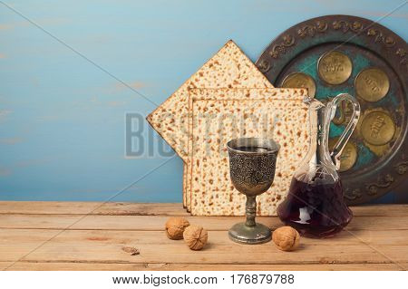 Jewish holiday Passover concept with wine matza and seder plate on wooden table