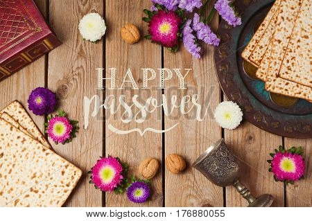 Jewish holiday Passover greeting card with matza and seder plate over wooden background. View from above