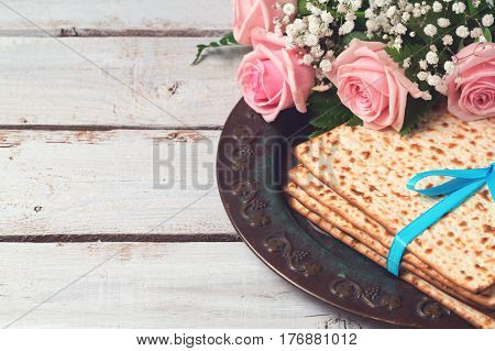 Jewish holiday Passover Pesah celebration with matzoh and rose flowers over wooden background with copy space