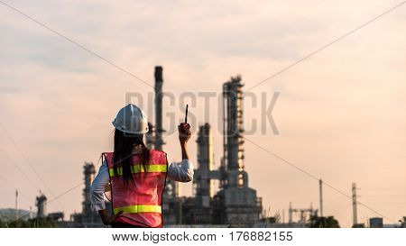 Double exposure of Engineer with safety helmet in front of Oil refinery and gas industry - refinery at sunset background Business Insustrail concept.