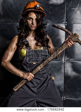 sexy female miner worker with pickaxe, in coveralls over a a body.