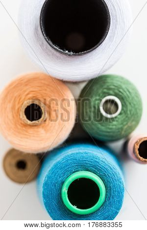 Concept of blurred colored threads for sewing. different sizes of the color bobbin of thread lying on a white background. top view. flat lay.