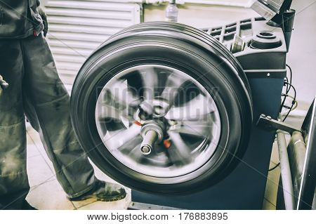 Mechanic worker makes computer wheel balancing on special equipment machine tool in auto repair service, toned photo with motion effect