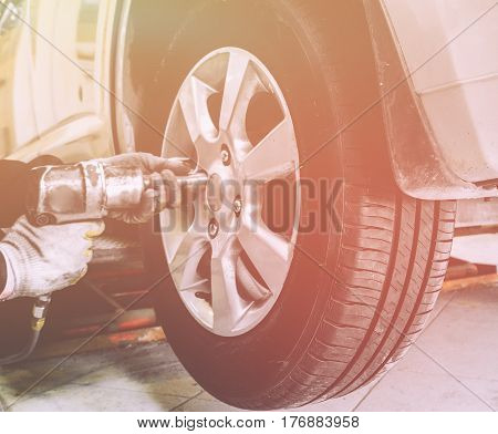 Close up of mechanic hands with pneumatic wrench changes wheel on car with special equipment in car repair service shop, sunlight effect