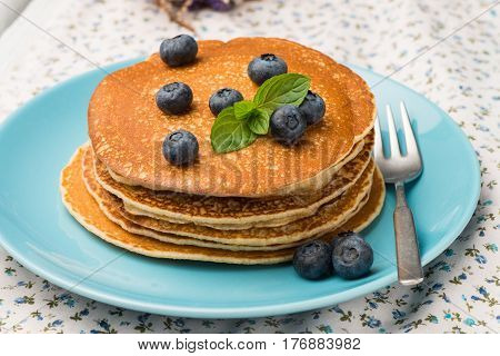Closeuip of delicious golden pancakes with fresh black berries.