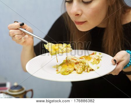 Young beautiful female about to eat scrambled eggs holding a fork and plate in her hands. Indoor cropped shot