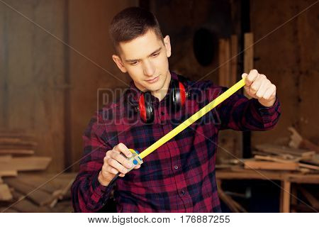 Workman Dressed In The Checkered Shirt Working With Tape-measure At The Sawmill. Timbers On Backgrou
