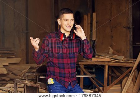 Smiling Workman Dressed In The Checkered Shirt Talking The Phone At The Sawmill. Timbers On Backgrou